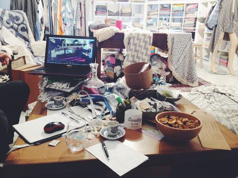Image of messy rooms full of clothes, papers, threads.