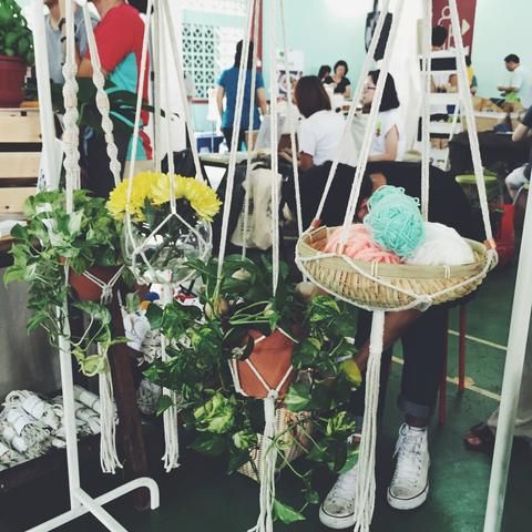 Image of hanging baskets consist of a bundle of yarns and flowers.