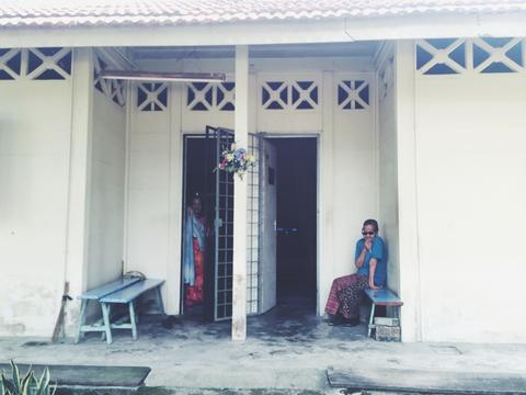 Imgae of two ladies sitting in front of their house by the doors.